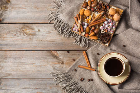 Autumn, fall, winter home decor in scandinavian, hygge style. Seasonal composition with cup of coffee, spices, warm woolen scarf, soft plaid on a rustic wooden table. Flat lay, copy space background