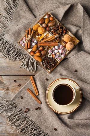Herbst, Herbst, Winter Wohnkultur im skandinavischen Hygge-Stil. Saisonale Komposition mit Tasse Kaffee, Gewürzen, warmem Wollschal, weichem Plaid auf einem rustikalen Holztisch. Flacher Hintergrund Standard-Bild