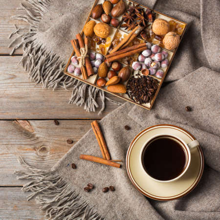Autumn, fall, winter home decor in scandinavian, hygge style. Seasonal composition with cup of coffee, spices, warm woolen scarf, soft plaid on a rustic wooden table. Flat lay background 写真素材