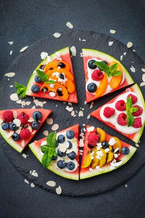 Alimentación sana y limpia, dieta y nutrición, concepto de verano estacional. Pizza de sandía con bayas, frutas, yogur, queso feta en una mesa. Vista superior de fondo plano laico.