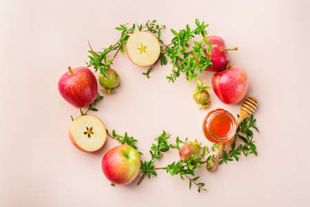 Rosh Hashana, jewish new year holiday concept with traditional symbols, apples, honey, pomegranate on a pastel pink, apricot table. Flat lay, copy space background Stok Fotoğraf