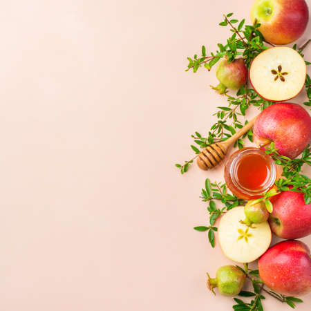 Rosh Hashana, jewish new year holiday concept with traditional symbols, apples, honey, pomegranate on a pastel pink, apricot table. Flat lay, copy space background