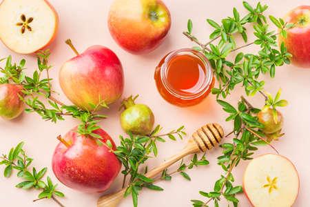 Rosh Hashana, concetto di festa di capodanno ebraico con simboli tradizionali, mele, miele, melograno su un tavolo rosa pastello, albicocca. Sfondo piatto Archivio Fotografico