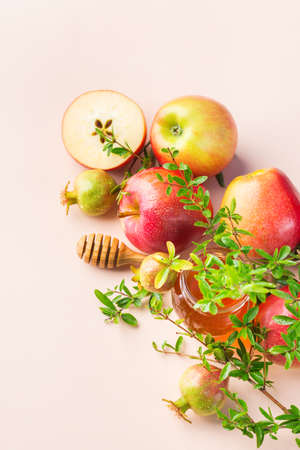 Rosh Hashana, jewish new year holiday concept with traditional symbols, apples, honey, pomegranate on a pastel pink, apricot table. Copy space background Banque d'images