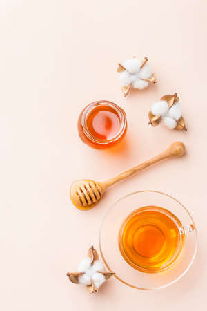 Cup of tea with honey on a trendy pastel pink, apricot background. Copy space, flat lay