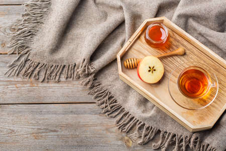 Autumn, fall, winter home decor in hygge style with drink. Seasonal composition with cup of hot tea with honey, warm woolen scarf, soft plaid on a rustic wooden table. Flat lay background