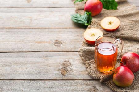 Eten en drinken, oogst herfst herfst concept. Vers biologisch appelsap in een mok met rijp fruit op rustieke houten achtergrond. Ruimte kopiëren