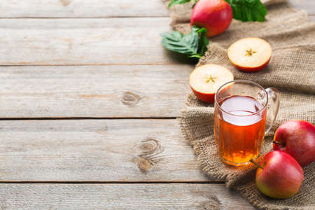 Food and drink, harvest autumn fall concept. Fresh organic apple juice in a mug with ripe fruits on rustic wooden background. Copy space