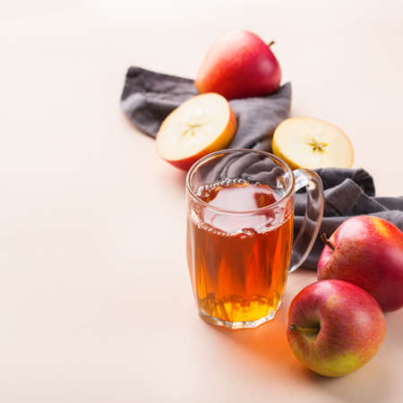 Food and drink, harvest autumn fall concept. Fresh organic apple juice in a mug with ripe fruits on trendy pink coral background. Copy space