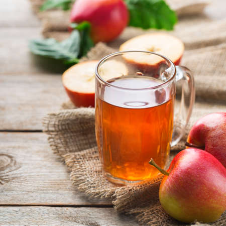 Food and drink, harvest autumn fall concept. Fresh organic apple juice in a mug with ripe fruits on rustic wooden background