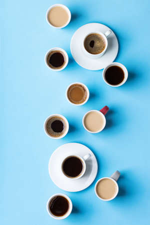 Assortment of coffee cups and mugs with black roasted, americano, cappuccino, milk on a blue background. Creative trendy flat lay