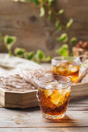 Old fashioned italian cocktail negroni with dry gin,  martini rosso vermouth and ice on a wooden table. Summer refreshing beverage