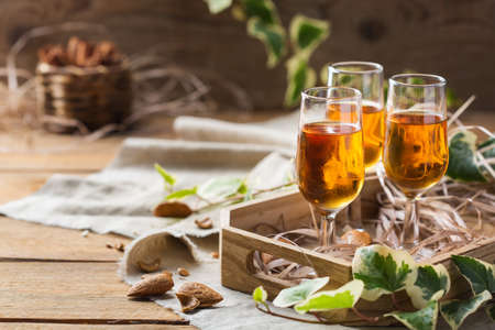 Holidays, alcohol drink, beverage, digestif concept. Italian almond liquor amaretto on a wooden table