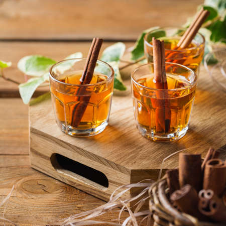 Holidays, alcohol drink, beverage, digestif concept. Shot with strong alcohol and cinnamon stick on a wooden table