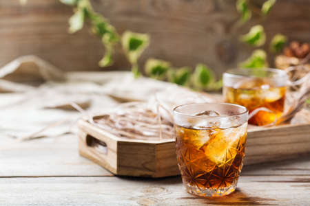 Old fashioned italian cocktail negroni with dry gin,   martini rosso vermouth and ice on a wooden table. Summer refreshing beverage Stok Fotoğraf