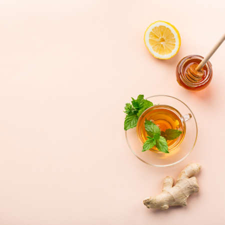 Warm drink beverage infusion in glass for cold flu winter fall days. Cup of ginger tea with mint, lemon and honey on a coral table. Copy space, flat lay background
