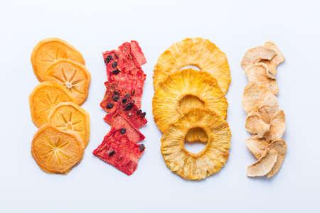 Alimentos saludables y equilibrados, alimentación limpia, bocadillos con sabor natural, concepto de ingredientes transparentes. Frutos secos, caqui deshidratado, sandía, piña, chips de manzana sobre un fondo blanco.