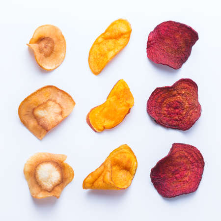 Healthy balanced food, clean eating, naturally flavoured snacks, transparent ingredients concept. Dried vegetables, dehydrated sweet potato, parsnip, beetroot chips on a white background
