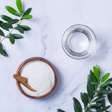 Collagen powder on a trendy marble background with green olive tree leaves. Natural beauty and health supplement, wellness skincare anti-aging concept. Top view, flat lay, copy space Stock Photo