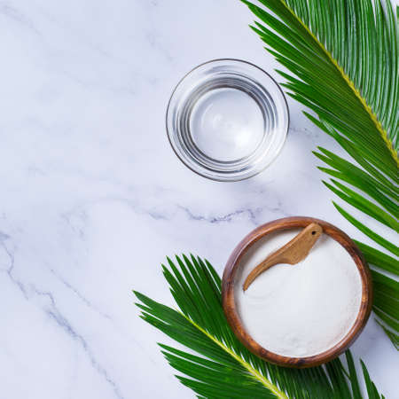 Collagen powder on a trendy marble background with green palm leaves. Natural beauty and health supplement, wellness skincare anti-aging concept. Top view, flat lay, copy space Stock Photo
