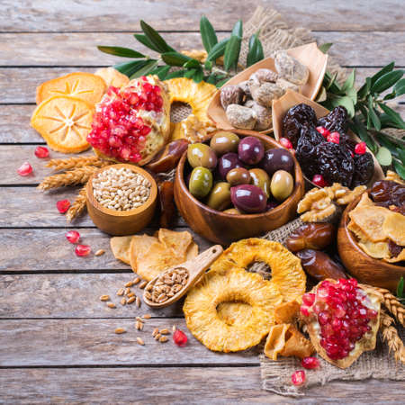 Symbols of judaic holiday Tu Bishvat, Rosh Hashana new year of the trees. Mix of dried fruits, date, fig, grape, barley, wheat, olive, pomegranate on a wooden table. Copy space background
