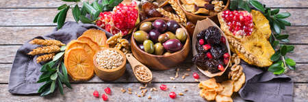 Symbols of judaic holiday Tu Bishvat, Rosh Hashana new year of the trees. Mix of dried fruits, date, fig, grape, barley, wheat, olive, pomegranate on a wooden table. Banner
