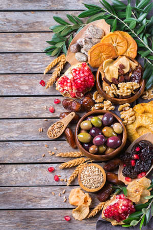 Symbols of judaic holiday Tu Bishvat, Rosh Hashana new year of the trees. Mix of dried fruits, date, fig, grape, barley, wheat, olive, pomegranate on a wooden table. Flat lay background