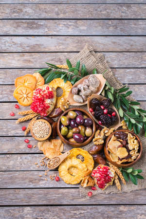 Symbols of judaic holiday Tu Bishvat, Rosh Hashana new year of the trees. Mix of dried fruits, date, fig, grape, barley, wheat, olive, pomegranate on a wooden table. Copy space flat lay background Banco de Imagens