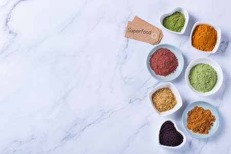 Balanced nutrition concept for clean eating antioxidant detox diet. Assortment of superfood powder - acai, turmeric, wheat, ginger, cinnamon, matcha. Flat lay, copy space marble background Stock Photo