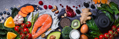 Balanced nutrition concept for clean eating diet. Assortment of healthy food, superfood ingredients for cooking on a kitchen table. Top view flat lay background, banner
