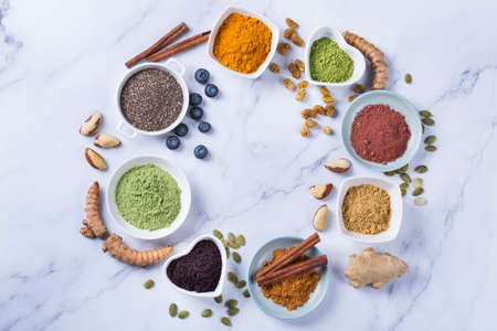 Balanced nutrition concept for clean eating antioxidant detox diet. Assortment of superfood powder - acai, turmeric, wheat, ginger, cinnamon, matcha. Flat lay marble background Stock Photo