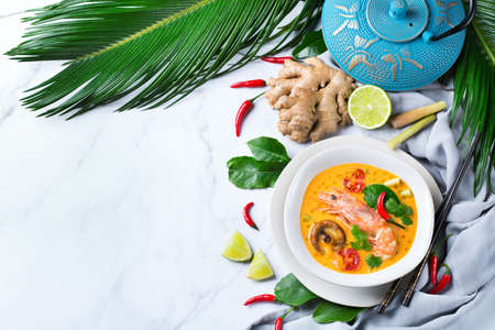 Food and drink, traditional Thai cuisine. Spicy tom yam kung, tom yum sour soup with shrimp, prawn, coconut milk, lemongrass and chili pepper in a bowl on a white table. Flat lay copy space Reklamní fotografie