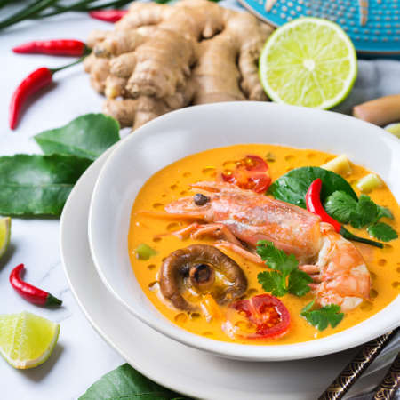Food and drink, traditional Thai cuisine. Spicy tom yam kung, tom yum sour soup with shrimp, prawn, coconut milk, lemongrass and chili pepper in a bowl on a white table