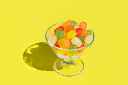 Colorful sugar candies - Akide Sekeri. Traditional Turkish sweets for Seker Bayram Ramadan holiday. Trendy sunny, vivid, hard light and shadows on yellow background. Copy space