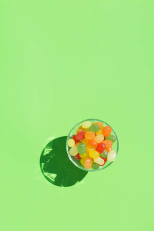 Colorful sugar candies - Akide Sekeri. Traditional Turkish sweets for Seker Bayram Ramadan holiday. Trendy sunny, vivid, hard light and shadows on green mint background. Top view flat lay copy space