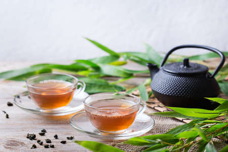 Cup of organic hot green tea on a wooden table with bamboo leaves