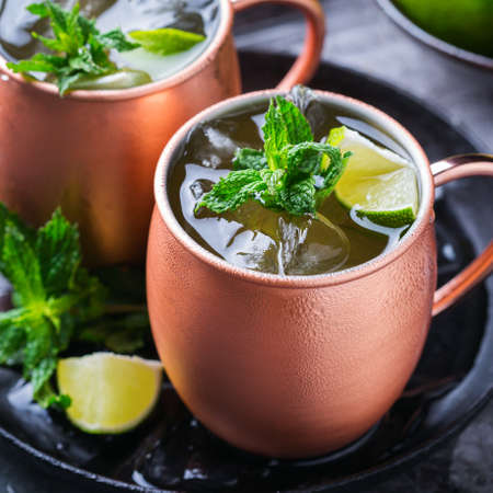 Classic Moscow mule cocktail with green lime, mint, ice in a copper mug on a black table.