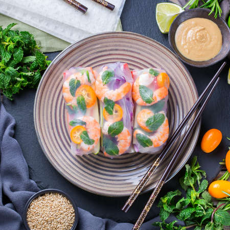Spring or summer rolls with rice paper, carrot, chili sauce, red cabbage, zucchini , pepper, shrimps and kumquats. Tasty asian food. Top view flat lay background