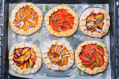 Assortment of fruit and vegetables, sweet and savoury  homemade small galette, tart, seasonal summer open pie with aromatic herbs. Healthy and tasty bakery product with ripe produce