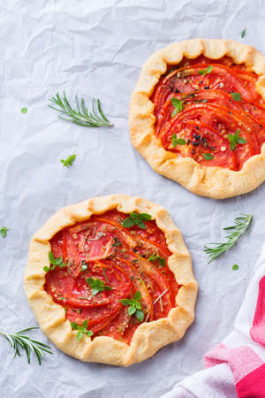 Small savoury homemade vegetarian tomato galette, tart, seasonal summer open pie with aromatic herbs. Healthy and tasty bakery product, dessert with ripe fruits.