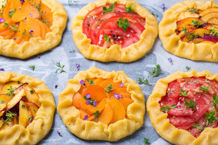 Assortment of raw fruit and vegetables homemade small galette, tart, seasonal summer open pie with aromatic herbs ready for oven. Healthy and tasty bakery product with ripe produce