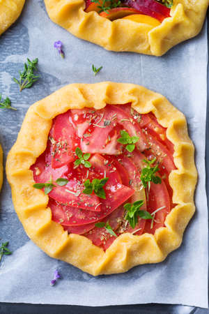 Raw vegetarian tomato homemade small galette, tart, seasonal summer open pie with aromatic herbs ready for oven. Healthy and tasty bakery product with ripe produce