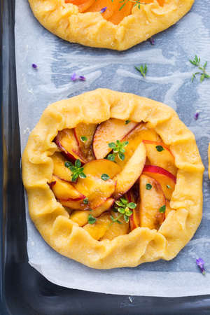 Raw vegetarian nectarine homemade small galette, tart, seasonal summer open pie with aromatic herbs ready for oven. Healthy and tasty bakery product with ripe produce Reklamní fotografie