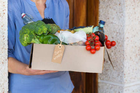 Zero waste no plastic home delivery service. Senior woman holding in hands box of food in recyclable and reusable, eco friendly package. Online internet order, shopping. Sustainable lifestyle concept