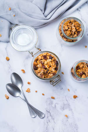 Healthy clean eating, dieting and nutrition, fitness, balanced food, breakfast concept. Homemade granola muesli with ingredients on a table. Top view flat lay background  Archivio Fotografico