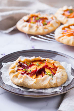 Homemade small nectarine, peach, apricot galette, tart, seasonal summer open pie with aromatic herbs. Healthy and tasty bakery product, dessert with ripe fruits.