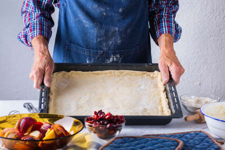 Baking, eating at home, healthy food and lifestyle concept. Senior baker man cooking, kneading fresh dough with hands, rolling with pin, spreading the filling on the pie on a kitchen table with flour 写真素材 - 154506278