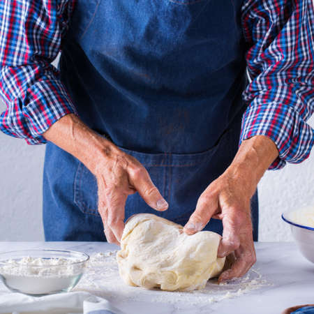 Baking, eating at home, healthy food and lifestyle concept. Senior baker man cooking, kneading fresh dough with hands, rolling with pin, spreading the filling on the pie on a kitchen table with flour 写真素材 - 154506279