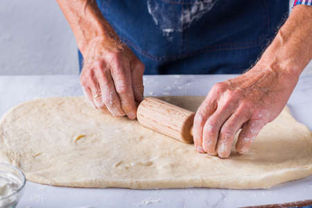 Baking, eating at home, healthy food and lifestyle concept. Senior baker man cooking, kneading fresh dough with hands, rolling with pin, spreading the filling on the pie on a kitchen table with flour 写真素材 - 154506280