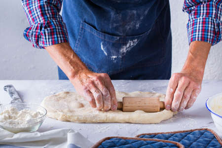 Baking, eating at home, healthy food and lifestyle concept. Senior baker man cooking, kneading fresh dough with hands, rolling with pin, spreading the filling on the pie on a kitchen table with flour 写真素材 - 154506291